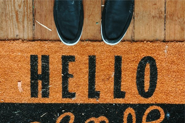 Feet by doormat saying hello